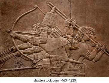 Ancient relief of assyrian warriors fighting in the war with bows,arrows and spears