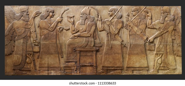 Ancient relief from Kalhu (Nimurid, Iraq) with Ashurnasirpal II king of Assyria on the throne with the Cup of sacrifice and is surrounded by a winged genius- patrons and courtiers