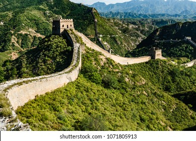 Ancient road along top of Great Wall of China split by an ancient tower leading down the mountain and green countryside