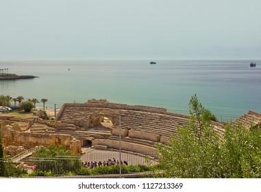 Ancient Roman amphitheatre of Tarragona with sea on the background in Tarragona, Catalonia, Spain
