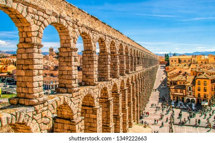 Ancient Roman aqueduct on Plaza del Azoguejo square and old building towns in Segovia, Spain.