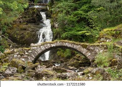 Ancient Roman bridge and waterfalls at Glen Lyon, Perthshire, Scotland.