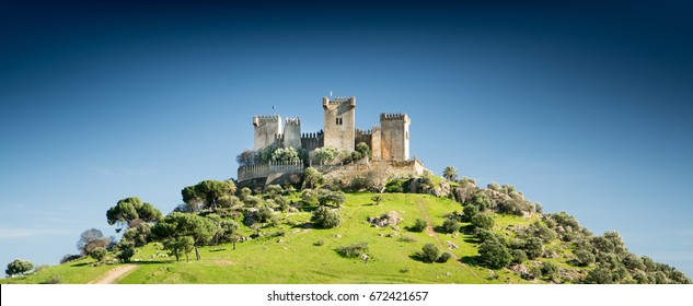 Ancient Roman castle on  green hill against a deep blue cloudless sky.  landscape format with copyspace. The castle is the Castillo de Almodovar del Rio near Cordoba in Spain.