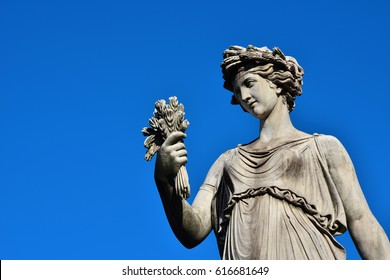 Ancient Roman or Greek neoclassical statue holding wheat in Rome (with copy space)