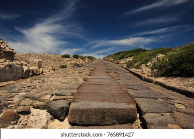 Ancient Roman road with large stone in foreground stretches into the distance under a deep blue sky at ruins of Tharros,  on the Sinis Peninsula, Sardinia