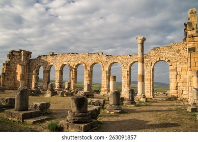 Ancient roman ruins in Morocco with white clouds and blue sky in the background