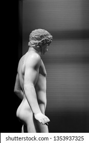 Ancient roman statue of nude young man in black and white