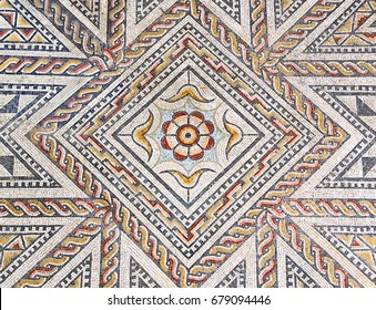 Ancient roman stone mosaic floor with geometric and floral design