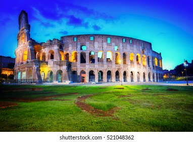 ancient Rome scene -  view of Colosseum with green lawn illuminated at night in Rome, Italy, toned
