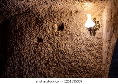 Ancient rough wall in cave with light from lamp in darkness. Antique lamp on scratched surface of limestone wall in cave of Cappadocia Turkey. Natural limestone textured background. Grunge backdrop.