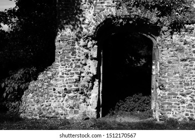An ancient ruin wall with a dark archway