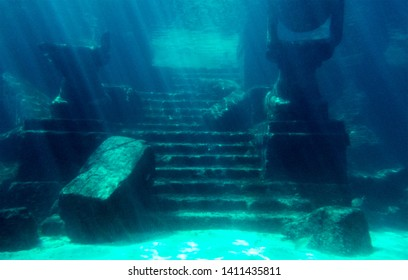 Ancient ruins with broken pieces under the tropical water of the Bahamas.