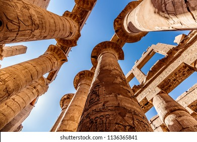 Ancient ruins and hieroglyphs at Karnak Temple, Luxor, Egypt. View from the ground to the high pillars.