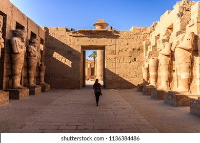 Ancient ruins and hieroglyphs at Karnak Temple, Luxor, Egypt. Female tourist photographed from behind in temple of Karnak, Luxor, Egypt.