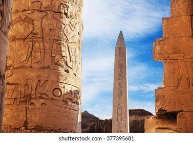Ancient ruins of Karnak temple in Egypt in the summer, Obelix and statues of Ramses II at the first pylon of the Luxor Temple (1279-1213 BC)
