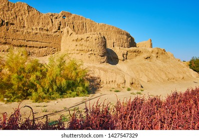 The ancient ruins of mud wall of Ghal'eh Jalali fortress, surrounded by plants of Mellat park, Kashan, Iran