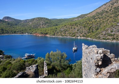 Ancient ruins on Gemiler Island and touristic boats over calm sea in Mugla province, Turkey. Archaeologists believe it was the location of the original tomb of Saint Nicholas