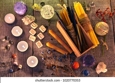 Ancient runes, candles, crystals, herbs and magic ritual objects on planks. Occult, esoteric and divination concept.