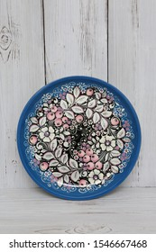Ancient russian traditional national handcraft: plate with blue north khokhloma painting with berries. Beautiful vintage wooden ware on white background. Best souvenir from Russia. Russian folk style