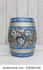 Ancient russian traditional national handcraft: keg with blue north khokhloma painting with berries. Beautiful vintage wooden ware on white background. Best souvenir from Russia. Russian folk style