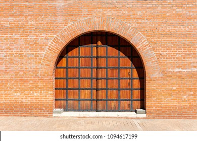 Ancient Russian wooden gate in a brick red wall of the Kremlin in Nizhny Novgorod