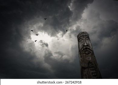 Ancient russian wooden idol against dramatic stormy cloudy sky with flying birds.