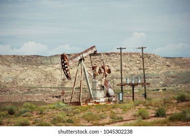 Ancient rusted, yet still functionning pumpjack in an oil field in a Southern Utah Landscape on the side of the road.