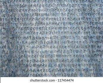 Ancient sanskrit text etched into a stone tablet.