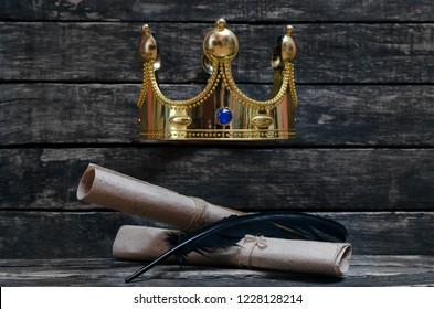 Ancient scrolls and quill pen under a golden king crown on wooden table. Royal decree concept. Luxury education.