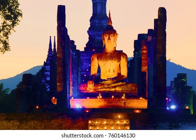 Ancient sculpture of the sitting Buddha on the ruins of the Buddhist temple of Wat Mahathat in the evening twilight. Sukhothai, Thailand