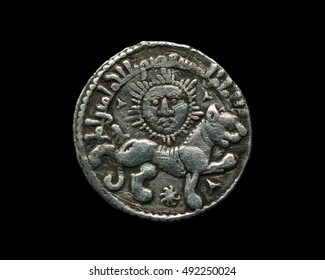 Ancient Seljuk silver coin with image of sun and lion isolated on black, close-up shot