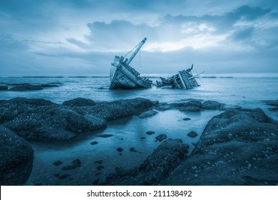 Ancient shipwrecks in the sea with sunset background blue color tone.