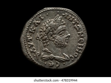 Ancient silver roman coin with portrait of emperor Caracalla, close-up shot, isolated on black