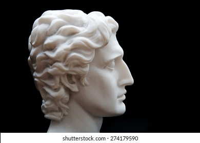 Ancient statue of Alexander the Great isolated on a black background