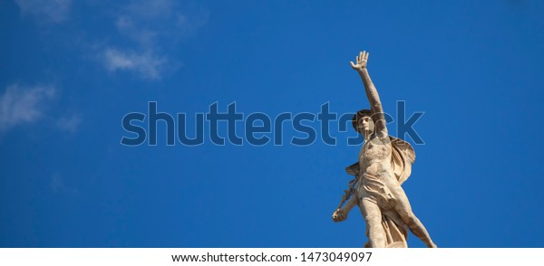 Ancient statue of the antique god of commerce, merchants and travelers Hermes (Mercury) against blue sky. He is alsow olympic gods messenger with wings on a helmet.