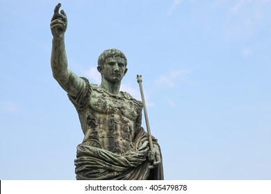 Ancient statue over blue sky. S.P.Q.R. IMP CAESAR Augustus PATRIAE PATER. Via dei Fori Imperiali street, Rome, Italy