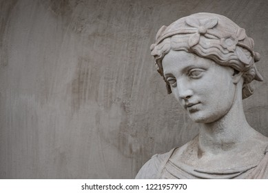 Ancient statue of sensual Greek renaissance era woman with a flower, Potsdam, Germany