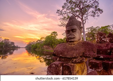 Ancient statues outside South Gate of Angkor Thom at sunset in Siem Reap, Cambodia