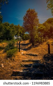 Ancient stepping stone stairs made by ancient greeks in the Sanctuary of the Great Gods on Samothrace Island in Greece against a blue sky