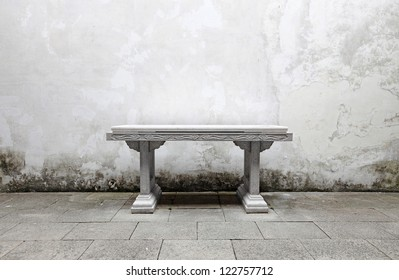 An ancient stone altar table against a grungy stained masonry wall.