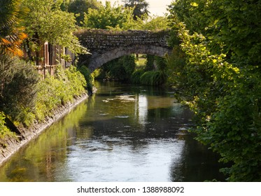 Ancient stone bridge crossing a canal in Aquileia, Italy