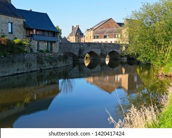 The ancient stone bridge in Ducey-les-Cheris reflected in the clear water of the River Selune.