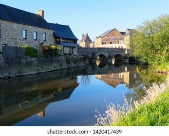 The ancient stone bridge at Ducey-les-Cheris is reflected in the still water of the River Selune.