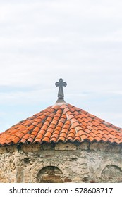 Ancient stone church with a tiled roof