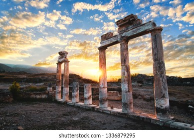Ancient stone columns of the gates of the Hierapolis, Pamukkale, Denizli province, Turkey. Sunrise with beautyful skyscape, ancient outdoor landscape view.