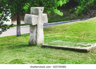 Ancient stone cross and tombstone in historic open-air museum