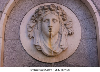 An ancient stone fountain with a woman's head adorned with a wreath of flowers. Fresh drinking water flowing out of her mouth. High quality photo