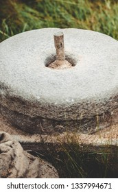 The ancient stone hand mill with grain. Medieval hand-driven millstone grinding wheat. Old quern stone hand mill with grain.