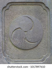 Ancient stone Japanese Shinto religion trinity symbol carving. Similar to the common ying yang, this triple symbol (called Tomoe) represents things in 3's including earth, heaven and the underworld.