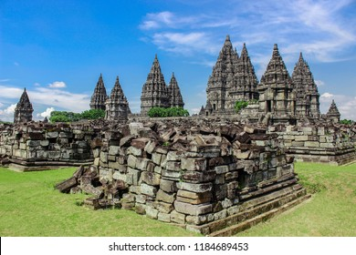 Ancient stone ruins on green field and Candi Prambanan or Rara Jonggrang, Hindu temple compound on background. Impressive architectural site. Yogyakarta, Central Java, Indonesia. Panoramic view.